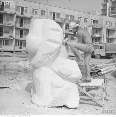 Rzeźbiarz Marek Jerzy Moszyński wykuwający lwa, który stanie przed szkołą na Puszczyka. Za rzeźbiarzem śliczny klasyczny Żuk. Tego obejrzeć dziś coraz trudniej. Zdjęcie ze zbiorów NAC, fot. Grażyna Rutowska.