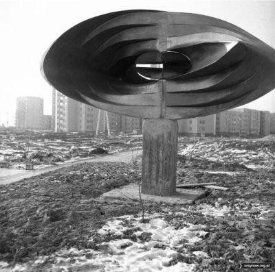 """Rzeźba znana jako """"oko"""" a oficjalnie """"Abstrakcja geometryczna"""" świeżo posadowiona na górce przy Wiolinowej. Za błotnistą drogą mamy bloki przy Pięciolinii. Fot. Włodzimierz Witaszewski"""