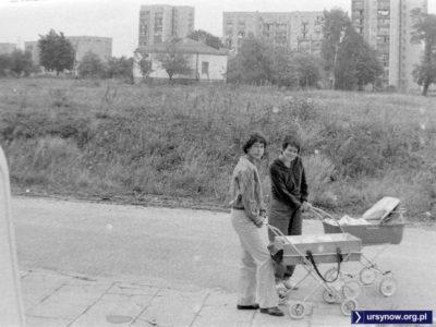 Dwóch małych Ursynowian z mamami na spacerze wzdłuż Wiolinowej. W tle cukiernia i koniec ulicy Puszczyka. Zdjęcie: Andrzej Herfurt.