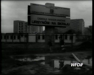 """Witacz na rogu Cynamonowej i Nugat (dziś Gandhi) stojący przed zapleczem budowy osiedla. Kadr z filmu """"Niczyje"""" J. Gębskiego, WFDiF"""