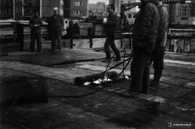 Robota pali się w rękach. Budowa stacji metra Stokłosy, robotnicy palnikiem rozgrzewają rozwinięte rolki papy. Za płotem ulice Bacewiczówny i ZWM. Zdjęcie Bartosz Dominiak.