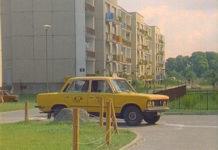 """Alternatywnych dróg sporo, ale żadna nie prowadzi do celu. Fiat 125p ze Zmiennikiem za kółkiem krąży po ulicy Lasek Brzozowy tytułowy zagajnik w tle i zmierza na filmowe Alternatywy 4. Kadr z serialu """"Zmiennicy""""."""