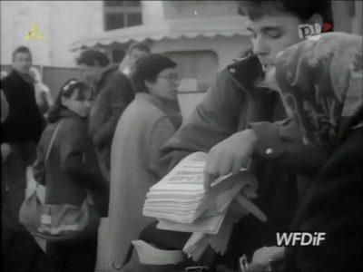 """Placyk przed Megasamem. Za redaktorem rozdającym """"Pasmo"""" czai się ozdobiony markizą Minipeweks, czyli sklep z Artykułami Zagranicznymi. Kadr z kroniki PKF 3/88."""