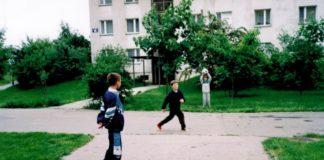 Podwórko przy ZWM 14 i klasycznie ubrany młody człowiek: kiep ten, kto w początkach lat dziewięćdziesiątych nie miał kreszowego szelest-dresu. Nad. Marta Szczepłek.