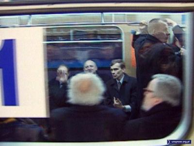 """Józef Oleksy uradowany macha do Narodu, odjeżdżając pociągiem numer jeden. W grudniu pociąg zatrzyma się na stacji """"Olin"""" i trzeba będzie wysiadać. Kadr z relacji TVP."""