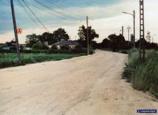 Ulica Nowoursynowska, po prawej widać fragmenty wytwórni asfaltu i bazy budowlanej przy Rosoła. A na słupie po lewej wspomnienie po kursującym tędy autobusie 104. Fot. Andrzej Kublik