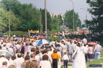 Procesja idzie już ulicą Bartoka w kierunku Jastrzębowskiego. Po lewej zwraca uwagę zaparkowany Jelcz z gustownym brezentem. Fot. Adam Myśliński.