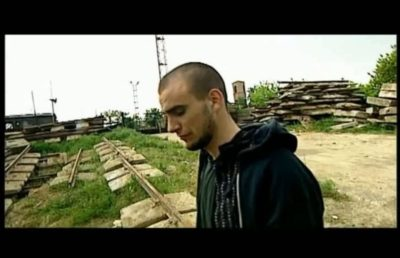 """To Fisz. Jeden z pierwszych ursynowskich hiphopowców opowiadający na tle Bazy Dźwigów, jak to się 10 lat temu wszystko zaczynało. Kadr z filmu S. Latkowskiego """"Blokersi""""."""