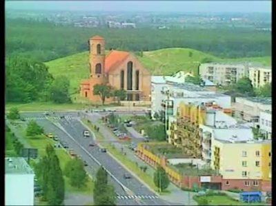 Kościół przy Stryjeńskich jeszcze w swojej surowej, pierwotnej formie. Na pierwszym planie ulica Belgradzka, a całość sfilmowana z wysokiego piętra Galerii Ursynów. Kadr z filmu promocyjnego dzielnicy.