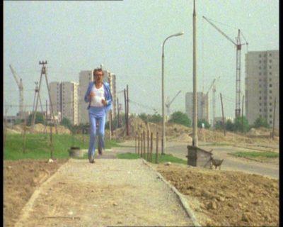 """Docent urządza sobie przebieżkę w dość trudnym terenie otaczającym bloki przy Grzegorzewskiej. A w tle powstają domy przy Lasku Brzozowym i Mandarynki. """"Alternatywy 4"""", odc. """"Spisek"""". Prod. TVP."""