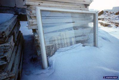 W zagrzebanym w śniegu oknie (nie wypaczy się?) z wybitą szybą odbijają się bloki Stokłosów. Widok z bazy budowlanej. 1977, fot. Włodzimierz Witaszewski.