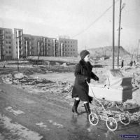 Ursynowska pionierka brnie z wózkiem błotnistym łącznikiem między Nutki i Końskim Jarem. A za nią wzgórze o kształcie nieokreślonym - to sypana właśnie Kopa Cwila. Fot. Włodzimierz Witaszewski.