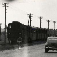 Rok 1963. Kolejka wąskotorowa na Puławskiej w kierunku Piaseczna. Zwróćcie uwagę także na dwóch cyklistów na eleganckich szosowych rowerach. Na pewno jadą szybciej niż pociąg. Zdjęcie ze zbiorów rodziny Pytko